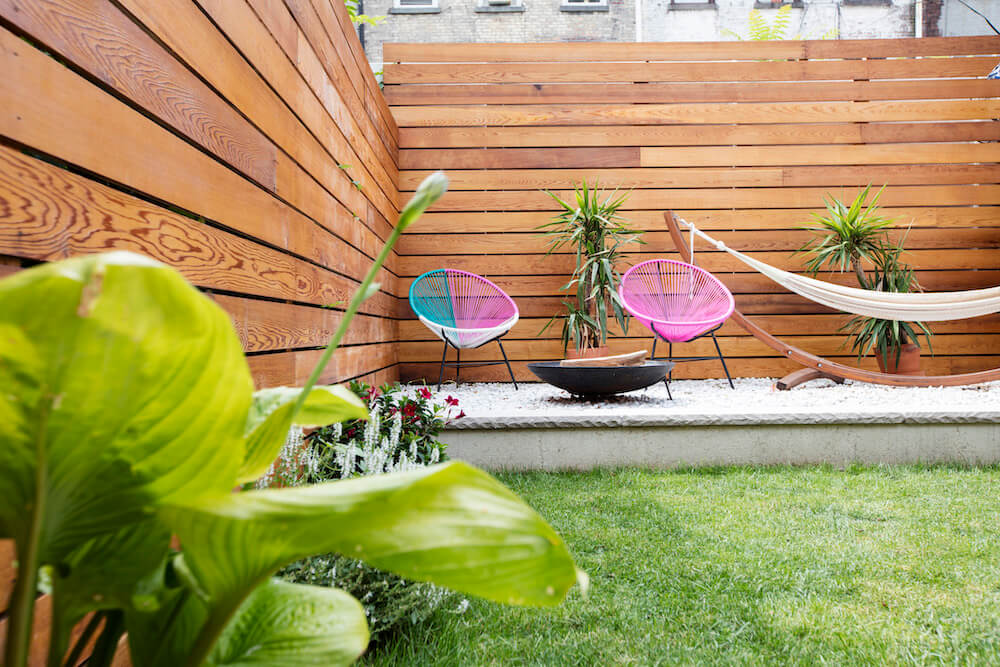 Image of a renovated backyard with full height wooden fence and outdoor chairs