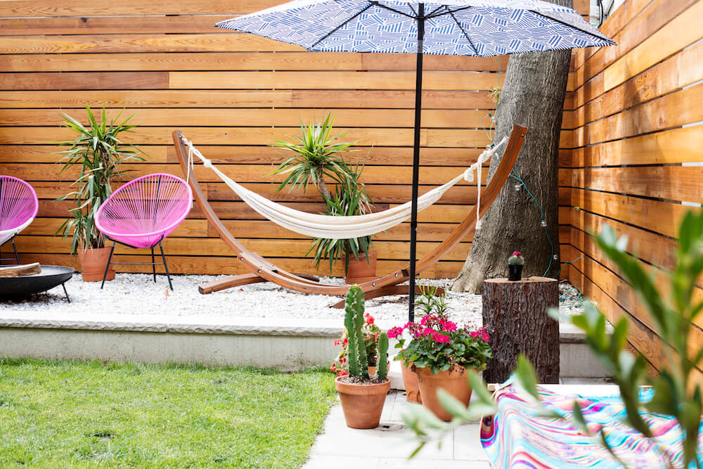 Image of a remodeled backyard with gravel lounge area and umbrella and hammock