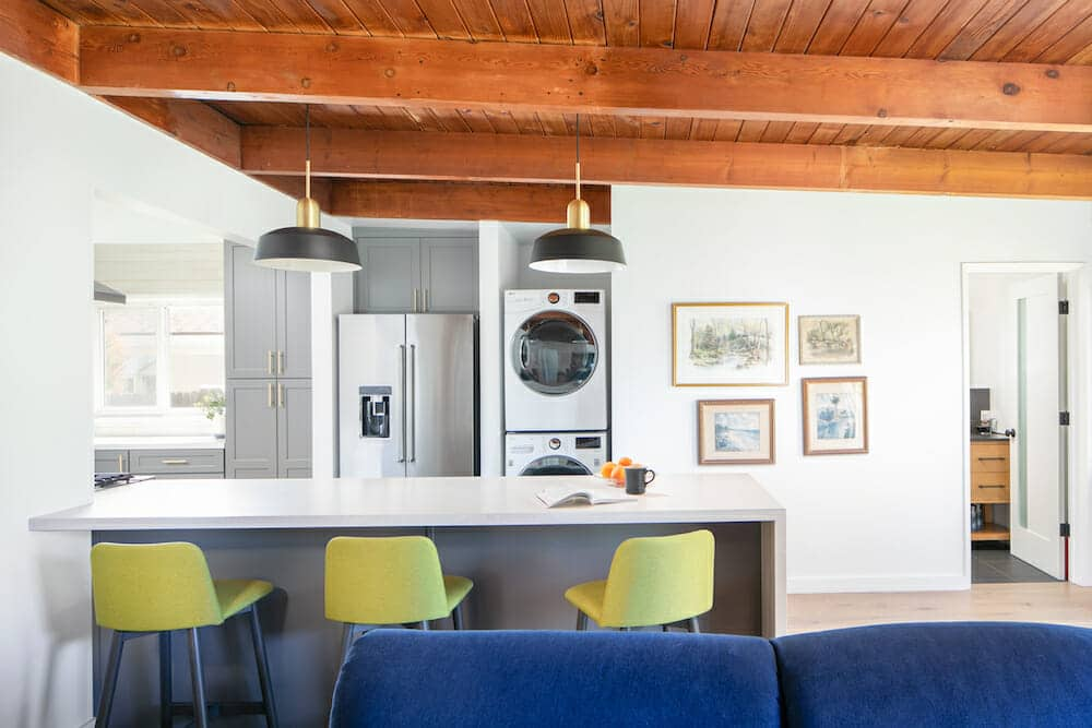 Modern kitchen with exposed beams and stacked washer dryer