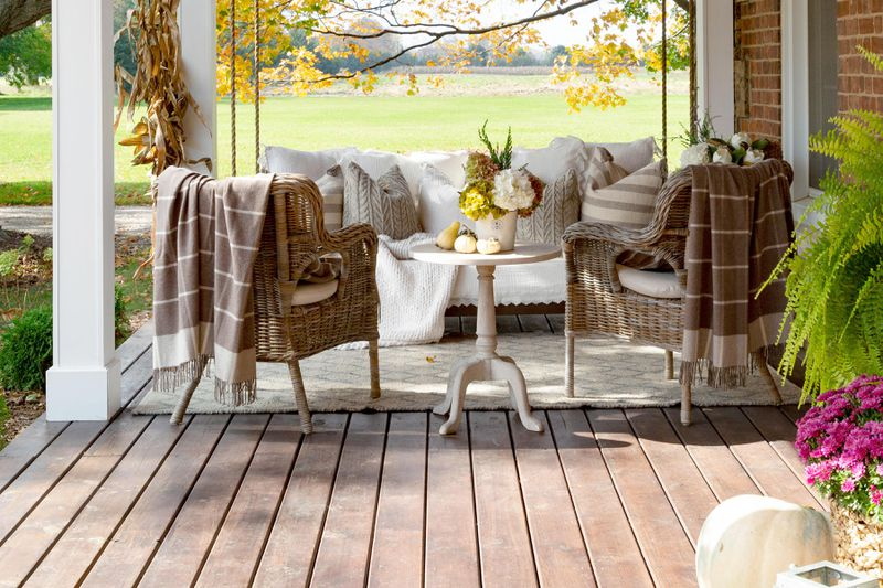 A front porch with a large swing, two wicker chairs and lots of cozy, warming decor.