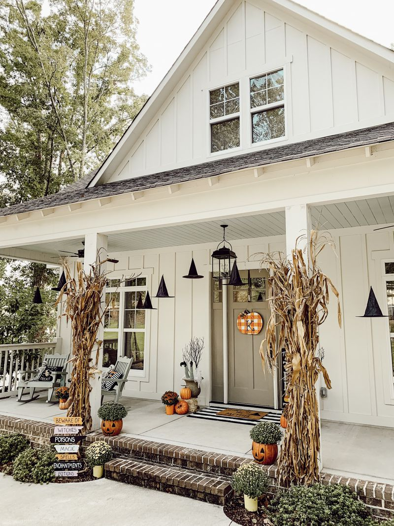 A not so spooky Halloween porch with floating hats, corn stalks and pumpkins.