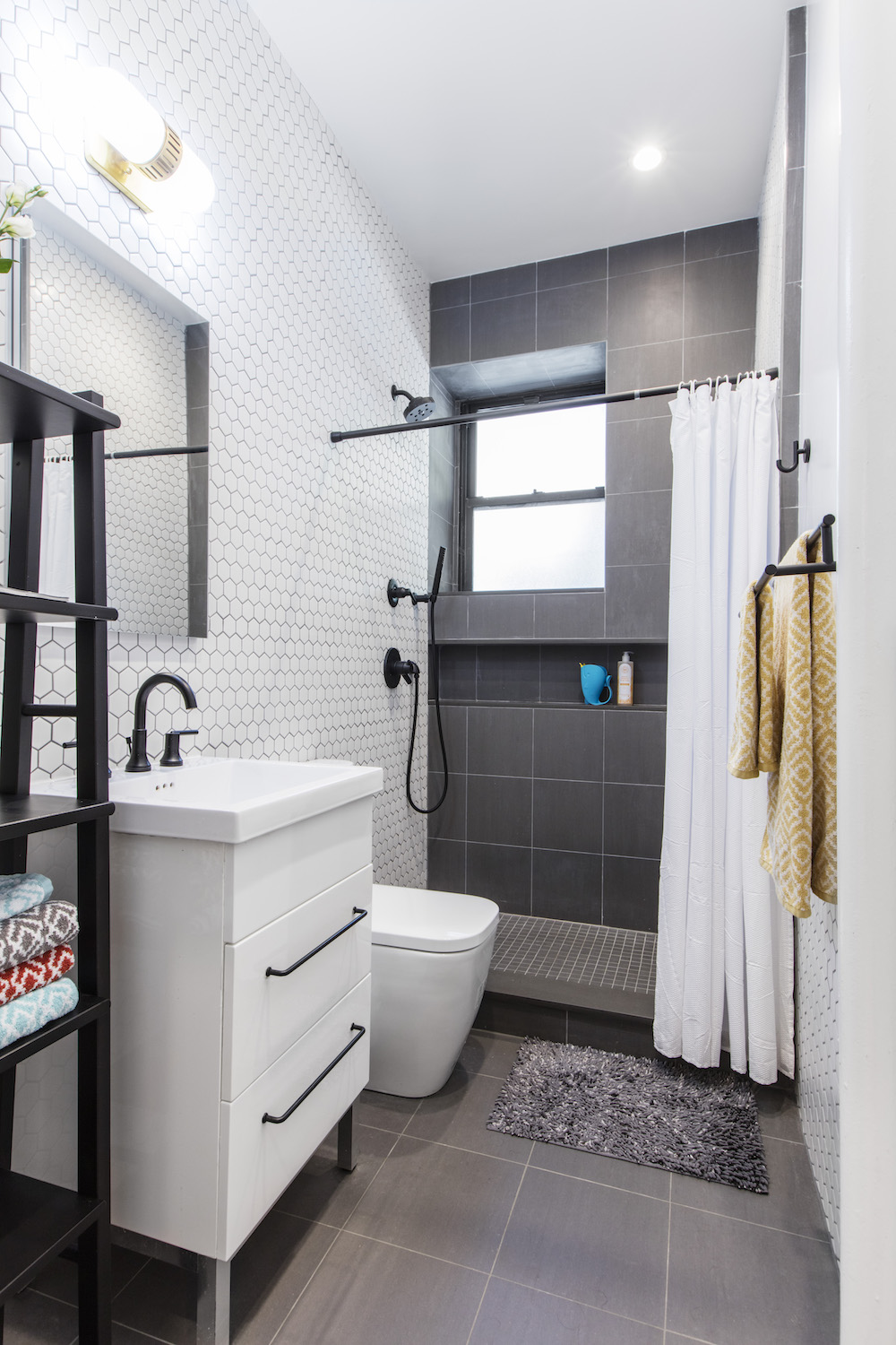 Bathroom with white tile walls, walk-in shower with gray tile and white bathroom vanity
